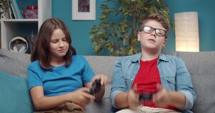 Boy and girl on couch with joysticks failing in video games