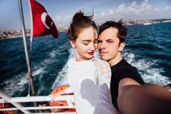 Boy and girl, couple. Make selfie on board a boat cruise vacation. Against the backdrop of the Turkish flag, the sea and Royalty Free Stock Photos