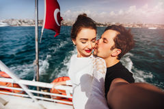 Boy and girl, couple. Make selfie on board a boat cruise vacation. Against the backdrop of the Turkish flag, the sea and Stock Images