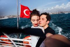 Boy and girl, couple. Make selfie on board a boat cruise vacation. Against the backdrop of the Turkish flag, the sea and Stock Photos
