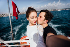 Boy and girl, couple. Make selfie on board a boat cruise vacation. Against the backdrop of the Turkish flag, the sea and Stock Photo
