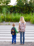 Boy and girl crossing the road observing traffic rules Stock Image