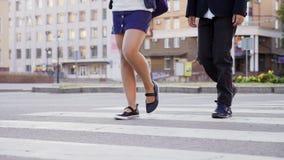 Boy and girl crossing street at crosswalk