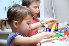 Boy and girl cutting paper for craft, brother and sister playing. Boy and girl making craft with paper with glue, kids brain development - siblings - brother and Royalty Free Stock Image