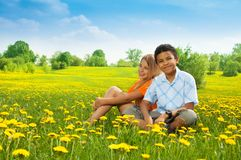 Boy and girl in dandelions Stock Image