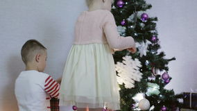 Boy and girl decorate a Christmas tree with snowflakes and flowers. stock video footage