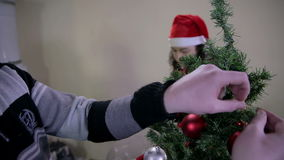 Boy and girl decorating Christmas tree stock footage