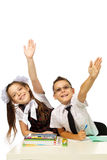 A boy and a girl at the desk raised their hands Royalty Free Stock Photography