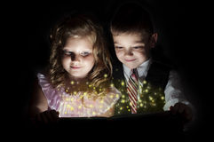 Boy and girl discover a magic book. Magic inside Royalty Free Stock Image