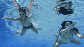 Boy and girl dive in swimming pool, slow motion