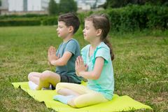 Boy and girl do yoga, eyes closed, outdoors, on a background of green grass, sitting on a gymnastic mat, side view royalty free stock images
