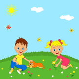 Boy, girl and dog on a meadow Stock Photo