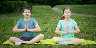 Boy and girl doing yoga, outdoors, on a background of green grass, sitting on a gymnastic mat stock photography