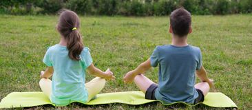 Boy and a girl doing yoga, outdoors, sitting on Mat. A boy and a girl doing yoga, outdoors, sitting on Mat royalty free stock photos
