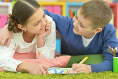 Boy and a girl draw with pencils Royalty Free Stock Image
