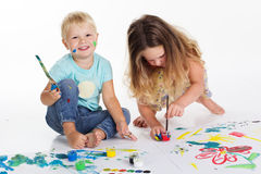 Boy and girl are drawing by aquarelle paints. Two happy child boy and girl are having fun and drawing pictures by aquarelle paints, isolated on white, studio Stock Images