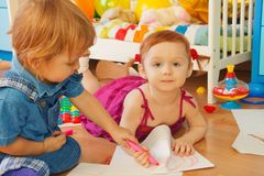 Boy and girl drawing with crayons Stock Images