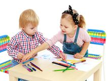Boy and girl drawing with pencils sitting at the Royalty Free Stock Images