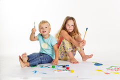 Boy and girl are drawing pictures by paints Royalty Free Stock Image