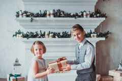 Boy and girl dressed elegantly standing in a bright room by the fireplace. Christmas tree in the background. New year concept. stock photos