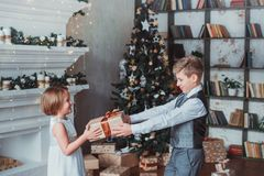 Boy and girl dressed elegantly standing in a bright room by the fireplace. Christmas tree in the background. New year concept. royalty free stock photos