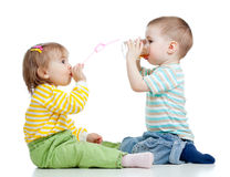 Boy and girl drinking juice from glass Stock Images