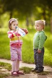 Boy and girl drinking mineral water in park Royalty Free Stock Image
