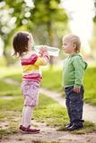 Boy and girl drinking mineral water in park Stock Photography