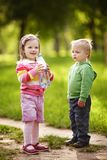 Boy and girl drinking mineral water in park Stock Images