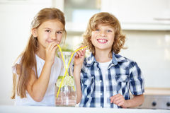 Boy and girl drinking water with straw Stock Photos