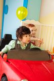 Boy and girl drive toy car Stock Image