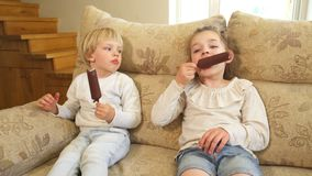 Boy and girl eat ice cream with chocolate on sticks sit on sofa. Handheld shot. Boy and girl eat ice cream with chocolate on sticks sitting on sofa at home stock video footage