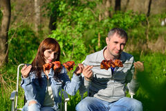 The boy and the girl eat a shish kebab on a skewer Stock Photo
