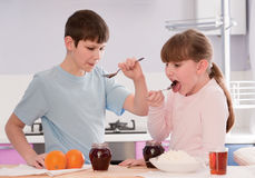 Boy and Girl eating breakfast cereal at home Royalty Free Stock Photos