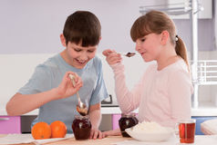 Boy and Girl eating breakfast cereal at home Royalty Free Stock Image