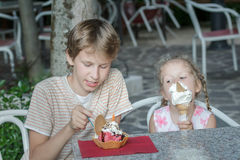 Boy and girl eating Italian gelato in street ice cream bar Royalty Free Stock Images