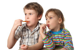 Boy and girl eating lollipops and looking at left Royalty Free Stock Images