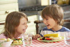 Boy And Girl Eating Meal In Kitchen Royalty Free Stock Photos