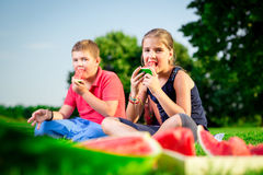 Boy and a girl eating watermelon on a sunny day Royalty Free Stock Photos
