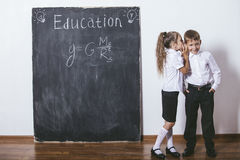 Boy and girl of elementary school in class background slate Royalty Free Stock Photography