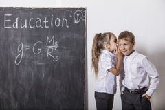 Boy and girl of elementary school in class background slate Royalty Free Stock Photo