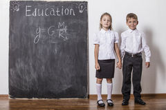 Boy and girl of elementary school in class background slate Stock Images