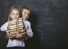 Boy and girl from elementary school in the classroom with books. Happy boy and girl from elementary school in the classroom with books in hands on a background Royalty Free Stock Photo