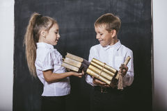 Boy and girl from elementary school in the classroom with books. Happy boy and girl from elementary school in the classroom with books in hands on a background Stock Photos