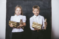 Boy and girl from elementary school in the classroom with books. Happy boy and girl from elementary school in the classroom with books in hands on a background Royalty Free Stock Image