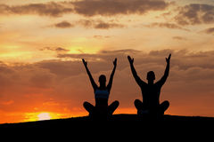 Boy and girl engage in yoga on the nature. Stock Photo