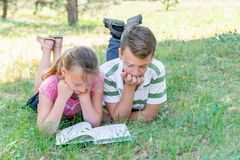 A boy and a girl are engaged in education, classmates together read from one textbook, the book lies on the grass stock image