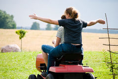 Boy and girl enjoy driving a tractor Stock Photo