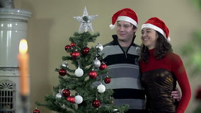 Boy and girl enjoying Christmas tree decorating in slow motion stock video footage
