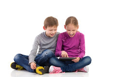Boy and girl enjoying new tablet Royalty Free Stock Photography